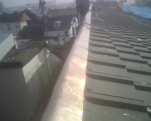 Copper ridge plate installed on roof to control moss growth